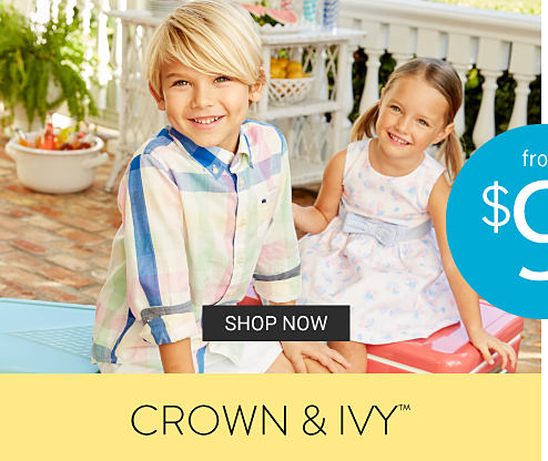 A boy wearing a yellow, blue & red plaid long sleeved button front shirt & white shorts sitting next to a girl wearing a multi colored sleeveless dress. From $9 Crown & Ivy. Shop now.