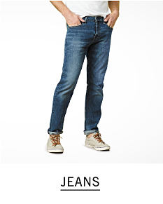 A man wearing a white T shirt, blue jeans & gray sneakers. Shop jeans.