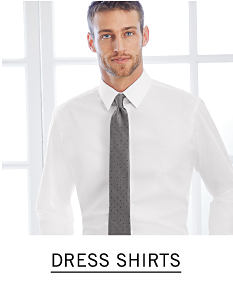 A man wearing a white dress shirt & a dark gray tie. Shop dress shirts.