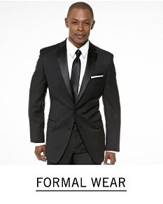 A man wearing a black suit, white dress shirt & black tie. Shop formal wear.