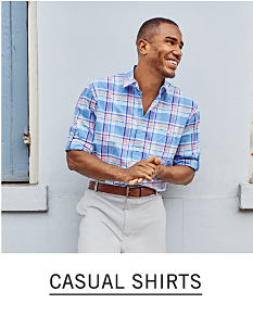 A man wearing a blue & white plaid long sleeved button front shirt & light gray pants. Shop casual shirts.