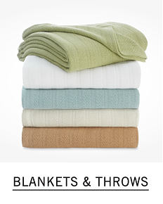 A stack of folded blankets in a variety of colors. Shop blankets and throws.
