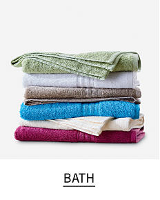 A stack of towels in a variety of colors. Shop bath.