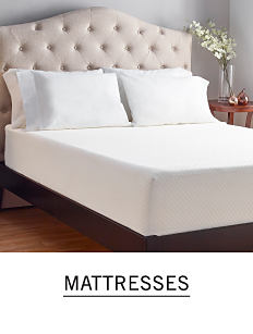 A bed with no bedding to show the mattress and sleeping pillows. Shop mattresses.