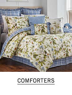 A bed with a floral comforter and pillows to match. Shop comforters.