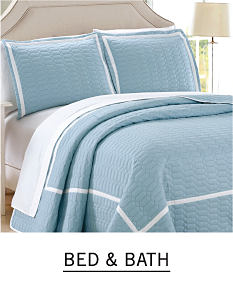 A bed with light blue bedding and pillows to match. Shop bed and bath.