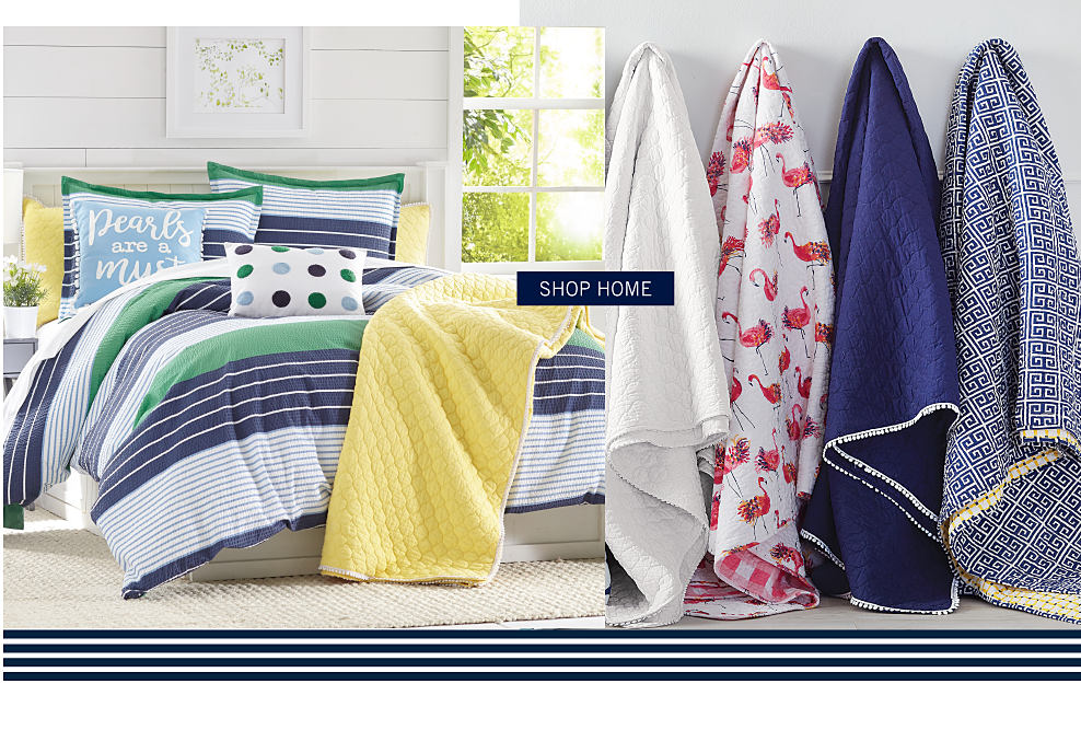 A bed made with a blue, white & green print comforter with coordinating pillows. An assortment of bath towels in a variety of colors & styles. shop home.