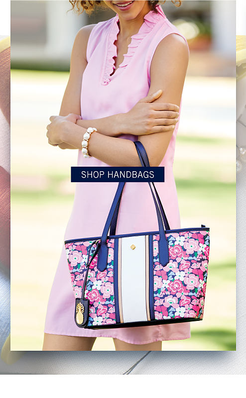 A woman wearing a light pink sleeveless dress carrying a multi colored floral print tote with blue handles & trim. Shop handbags.