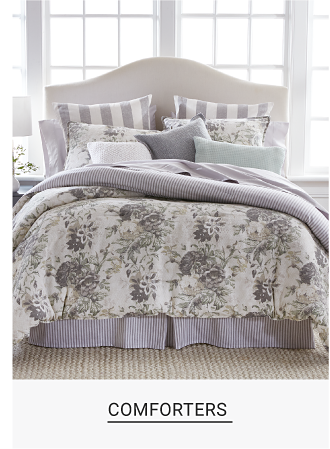 A bed made up with a white comforter with purple floral design and matching pillows. Comforters. Shop now.