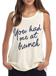 "A young woman wearing a graphic tank that reads ""You had me at brunch."" Shop tops."