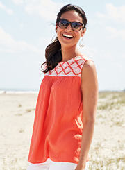 A woman wearing a coral top and white pants while standing on the beach. Shop tops.
