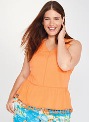 A young woman wearing an orange top and printed shorts. Shop tops.