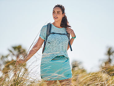 A woman wearing a blue top and skort while hiking outdoors.